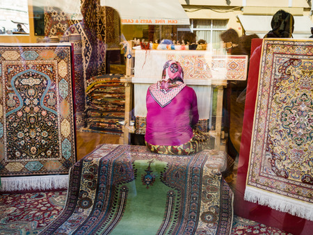 ISTANBUL, TURKEY - SEPTEMBER 10, 2010: Woman weave carpet in window of shop. Carpet weaving is one of the ancient crafts in Turkey, and traditionally women have played a pivotal role in their creation