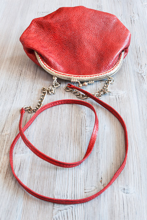 pochette: one little red leather womens handbag on wood table Stock Photo