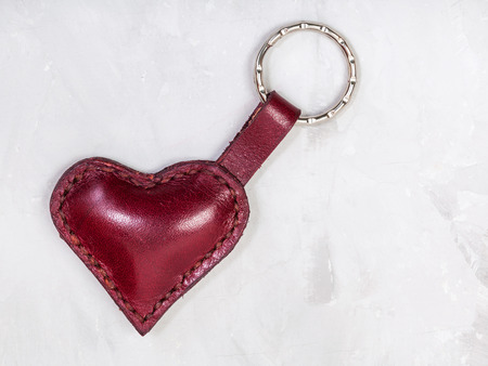 red leather heart shape keychain on concrete board Stock Photo