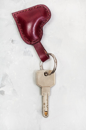 modern key with red leather heart shape keychain on concrete plate Stock Photo