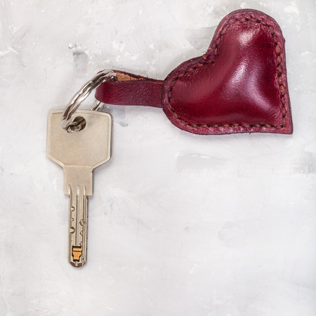 door key with red leather heart shape trinket on concrete plate