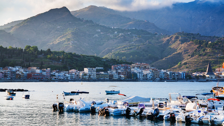 GIARDINI NAXOS, ITALY - JULY 6, 2011: boat mooring in Giardini Naxos town in evening. Naxos was founded by Thucles the Chalcidian in 734 BC, and since 1970s it has become a seaside-resort