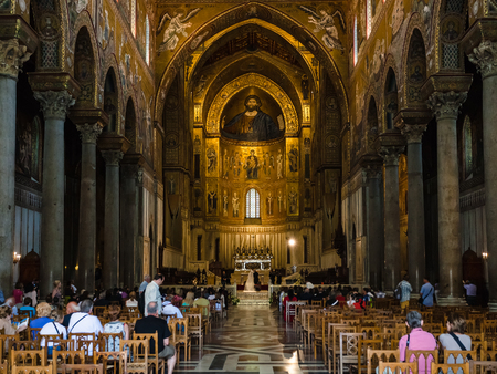 MONREALE, ITALY - JUNE 25, 2011: tourists indoor of Duomo di Monreale in Sicily. The cathedral of Monreale is one of the greatest examples of Norman architecture, it was begun in 1174 Editorial