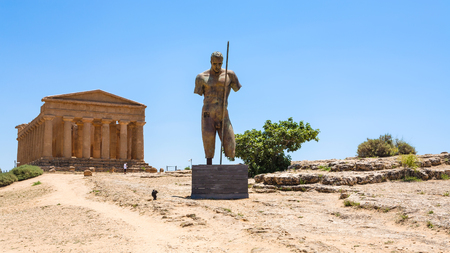 AGRIGENTO, ITALY - JUNE 29, 2011: statue and Temple of Concordia in Valley of the Temples in Sicily. This area has largest and best-preserved ancient Greek buildings outside of Greece itself Editorial