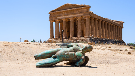 AGRIGENTO, ITALY - JUNE 29, 2011: sculpture and Temple of Concordia in Valley of the Temples in Sicily. This area has largest and best-preserved ancient Greek buildings outside of Greece itself