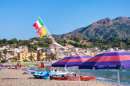 GIARDINI NAXOS, ITALY - JULY 8, 2011: flags over boats and people on urban beach of Giardini Naxos . Naxos was founded by Thucles the Chalcidian in 734 BC, and since 1970s it has become a seaside-resort
