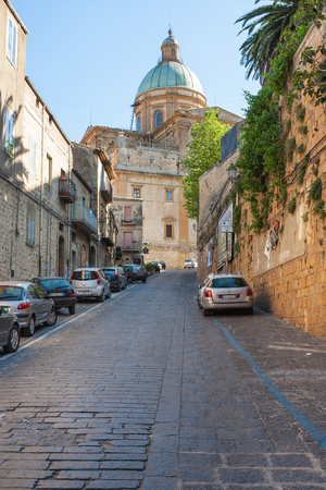 PIAZZA ARMERINA, ITALY - JUNE 29, 2011: street to Duomo Cathedral in Piazza Armerina town in Sicily. Baroque cathedral was built in 17th and 18th cent, on the 15th-cent foundations of former church