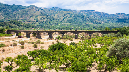 agricultural tourism in Italy - citrus garden and bridge in Alcantara river valley in Sicily