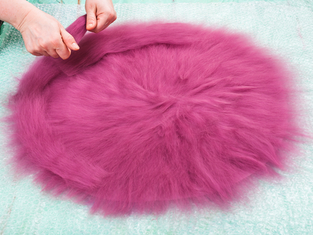 workshop of manufacturing of felt for beret in wet felting process - milliner spreads the second layer of wool fibers on hat layout Stock Photo