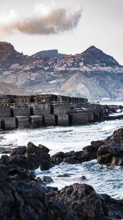 gloaming: Italy - stone breakwater in Giardini Naxos town in Sicily in evening Stock Photo