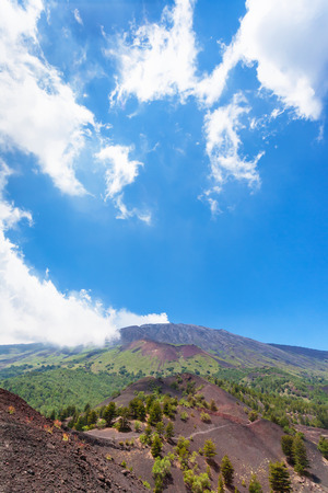 Italy - blue sky with white clouds over old craters of Etna volcano in Sicily