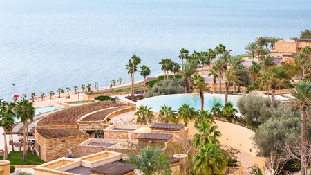 bordered: DEAD SEA, JORDAN - FEBRUARY 19, 2012: Kempinski spa resort hotel Ishtar and Dead Sea in winter season. The Dead Sea is is deepest hypersaline lake in the world bordered by Jordan, Israel and Palestine