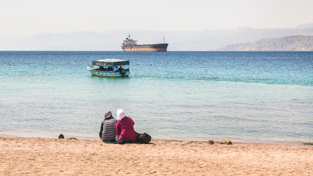 AQABA, JORDAN - FEBRUARY 23, 2012: muslim women on urban beach in sunny winter day. Jordan country has only one exit to sea in Gulf of Aqaba, the length of the coast is 27 km
