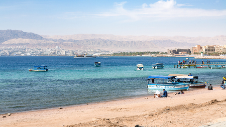 AQABA, JORDAN - FEBRUARY 23, 2012: Aqaba city beach and view of Eilat city in the background in winter day. Jordan country has only one exit to sea in Gulf of Aqaba, the length of the coast is 27 km Editorial