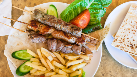 Travel to Middle East country Kingdom of Jordan - above view of skewers with various arabian kebabs in restaurant in Petra town