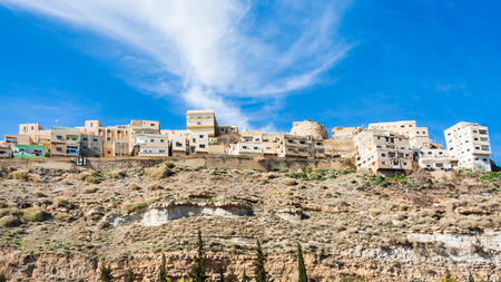 Travel to Middle East country Kingdom of Jordan - bottom view of Al-Karak town on top of hill in sunny winter day