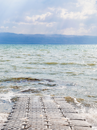 Travel to Middle East country Kingdom of Jordan - pontoon pier on coast of Dead Sea in winter Stock Photo