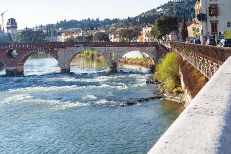 VERONA, ITALY - MARCH 27, 2017: view of Ponte Pietra Roman arch bridge (Stone Bridge, Pons Marmoreus) on Adige River in spring. Verona is city on the Adige river, one of the seven provincial capitals of Veneto region Stock Photo - 76621090