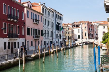 reside: VENICE, ITALY - MARCH 30, 2017: people on waterfront of canal Rio San Lorenzo in Venice in spring. The city has about 50,000 tourists a day and only around 55,000 people reside in the historic town