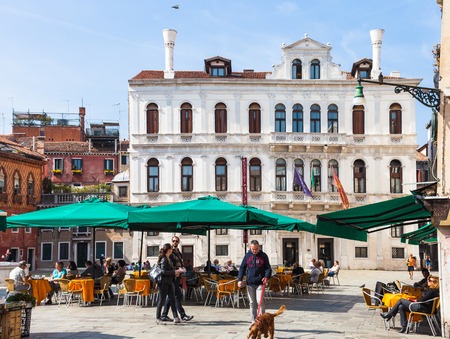 reside: VENICE, ITALY - MARCH 30, 2017: people on square Campo Santa Maria Formosa in Venice in spring. The city has about 50,000 tourists a day and only around 55,000 people reside in the historic town