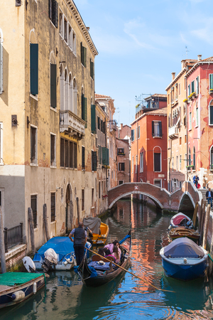reside: VENICE, ITALY - MARCH 30, 2017: tourists in gondolas on canal Rio del Mondo Novo in Venice city. The city has about 50000 tourists a day and only around 55000 people reside in the historic town Editorial