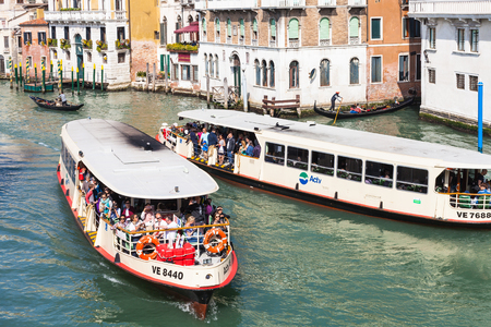 VENICE, ITALY - MARCH 30, 2017: view of water buses with tourists in Grand Canal in Venice city from Rialto bridge in spring. The Grand Canal forms one of the major water-traffic corridors in the city Editorial