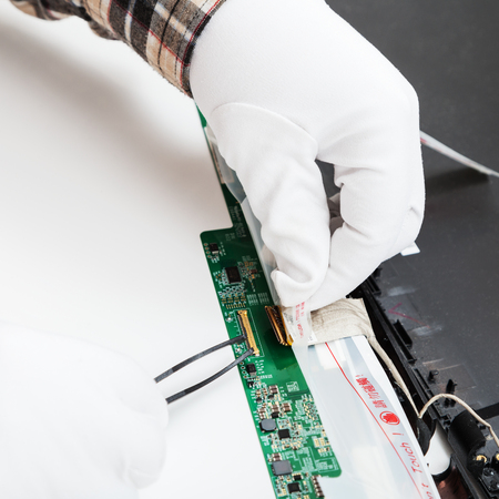 disassembling of laptop - serviceman in white gloves replaces LCD screen
