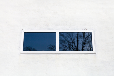 glass window in white painted wall of country house