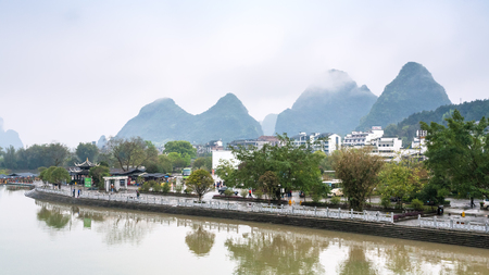 YANGSHUO, CHINA - MARCH 29, 2017: waterfront of Yulong river in Yangshuo town county in spring. Town is resort destination for domestic and foreign tourists because of scenic karst peaks Editorial