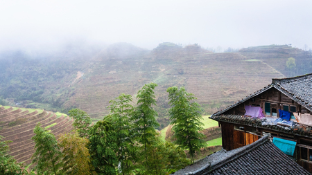 travel to China - houses in Tiantouzhai village and terraced hills in area Dazhai Longsheng Rice Terraces (Dragons Backbone terrace, Longji Rice Terraces) country in spring
