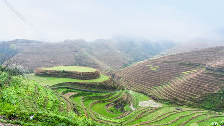 travel to China - above view of terraced rice gardens on hills from Tiantouzhai village in area Dazhai Longsheng Rice Terraces (Dragons Backbone terrace, Longji Rice Terraces) country in spring Stock Photo