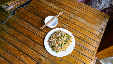 travel to China - above view of fried rice with vegetables on plate in rustic eatery in area Dazhai Longsheng Rice Terraces (Dragons Backbone terrace, Longji Rice Terraces) country in spring Stock Photo