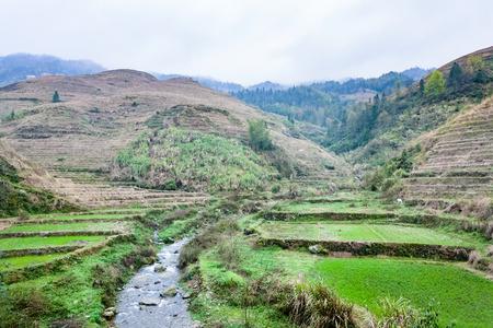 travel to China - water stream between terraced fields of Dazhai village in area of Longsheng Rice Terraces (Dragons Backbone terrace, Longji Rice Terraces) in spring season