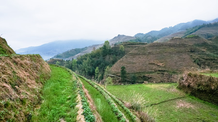 travel to China - terraced fields of Tiantouzhai village on hills in area of Dazhai Longsheng Rice Terraces (Dragons Backbone terrace, Longji Rice Terraces) in spring season