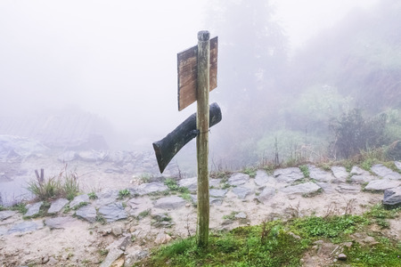 travel to China - direction sign on mountain path in misty spring day in area of Dazhai Longsheng Rice Terraces (Dragons Backbone terrace, Longji Rice Terraces)