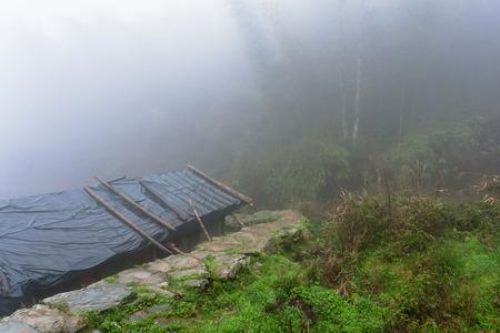 travel to China - fog over hut in Tiantouzhai village in Dazhai Longsheng Rice Terraces (Dragons Backbone terrace, Longji Rice Terraces) country in spring season