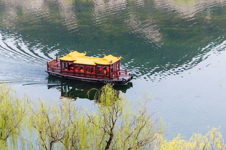 LUOYANG, CHINA - MARCH 20, 2017: above view of passenger boat in Yi river between West and East Hills of Chinese Buddhist monument Longmen Grottoes ( Longmen Caves) in spring season