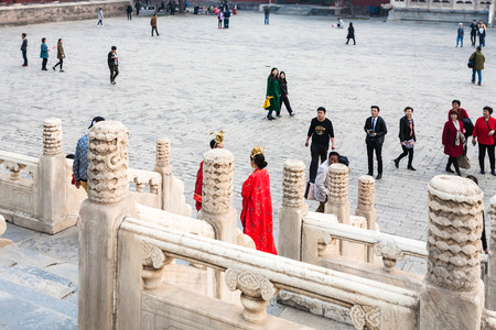 BEIJING, CHINA - MARCH 19, 2017: couple in red dresses and tourists on courtyard of Imperial Ancestral Temple (Taimiao, Working Peoples Cultural Palace) in Beijing Imperial city in spring