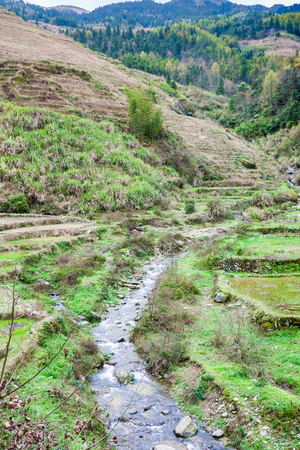 travel to China - view of terraced gardens and streem in Dazhai village in country of Longsheng Rice Terraces (Dragons Backbone terrace, Longji Rice Terraces) in spring Stock Photo
