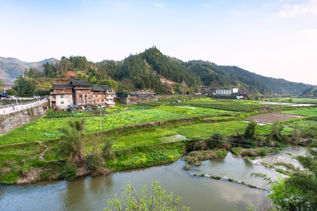 travel to China - view of gardens, rice paddy, tea plantation near river in Chengyang village of Sanjiang Dong Autonomous County in spring season Stock Photo