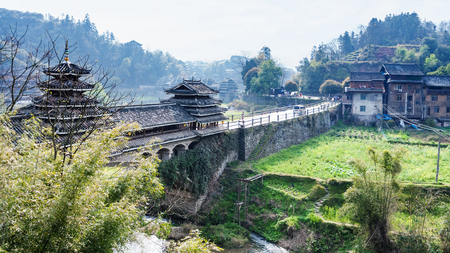 travel to China - view of Fengyu Bridge and gardens near river in Chengyang village of Sanjiang Dong Autonomous County in spring morning