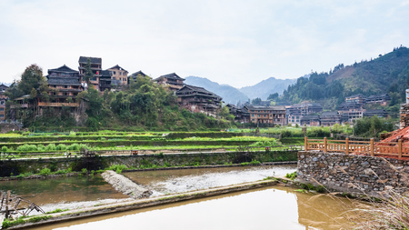 travel to China - view of terraced rice paddies and houses near irrigation canal in Chengyang village of Sanjiang Dong Autonomous County in spring season Stock Photo