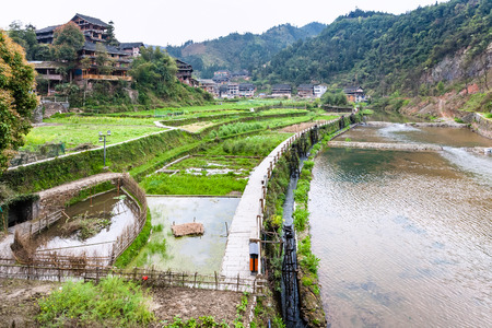 travel to China - view of irrigation canal and rice paddies in Chengyang village of Sanjiang Dong Autonomous County in spring season