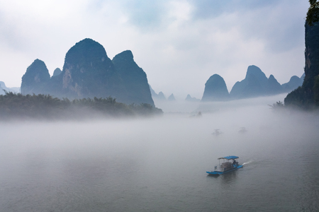 travel to China - view of fog with ships on river near Xingping town in Yangshuo county in spring morning