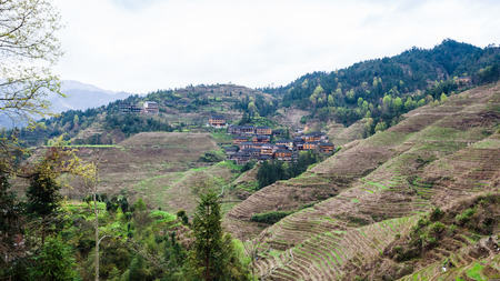 travel to China - view of Dazhai village on green hills in area Longsheng Rice Terraces (Longji Rice Terraces) in spring