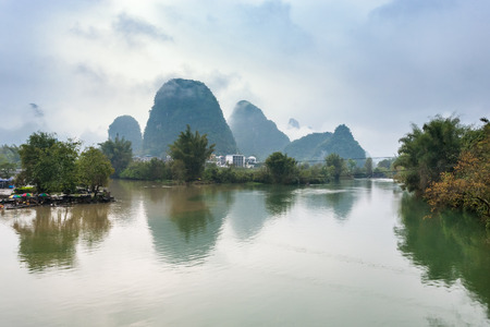 riverbank: travel to China - calm surface Yulong and Jinbao river and karst peaks in Yangshuo County in spring season