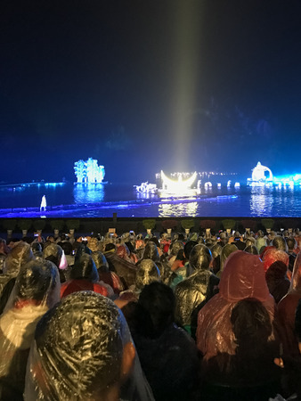 陽朔, 中国 - 2017 年 3 月 28 日: 漓江陽朔市では雨の中での夜の光のショーの人々。町は風光明媚なカルスト ピークのため国内および外国人観光客のリ 報道画像