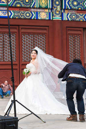 BEIJING, CHINA - MARCH 19, 2017: photographer and bride on courtyard of Imperial Ancestral Temple (Taimiao, Working Peoples Cultural Palace) in Beijing Imperial city in spring. Editorial