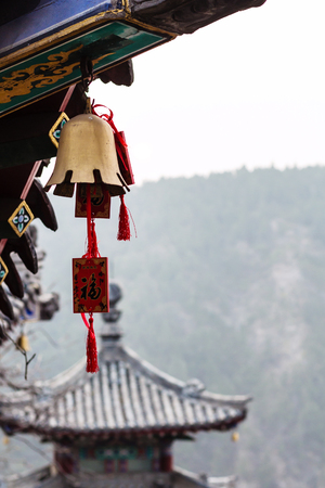 LUOYANG, CHINA - MARCH 20, 2017: bell and temple on East Hill of Chinese Buddhist monument Longmen Grottoes in spring. The complex was inscribed upon the UNESCO World Heritage List in 2000 Editorial