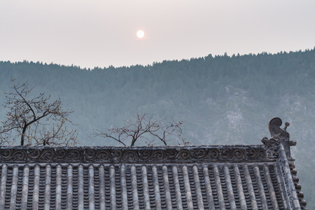 LUOYANG, CHINA - MARCH 20, 2017: sun over roof of pagoda on East Hill of Chinese Buddhist monument Longmen Grottoes in spring. The complex was inscribed upon the UNESCO World Heritage List in 2000